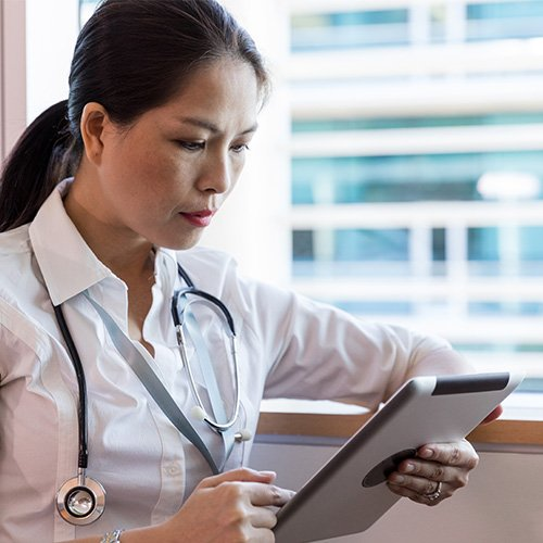 Female Asian doctor looking at a smart device while on her shift