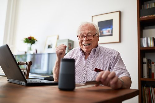 Senior man doing online shopping using a credit card, laptop and smart speaker device.