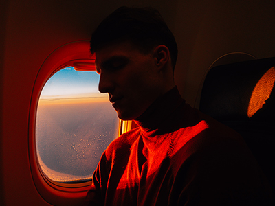 Side view of young handsome male sleeping in aircraft over window with sunset