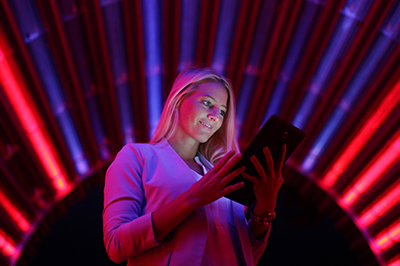 Businesswoman with tablet pc against high tech lights background