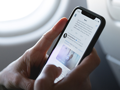 Image of a person using a smartphone on a plane.
